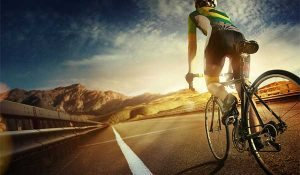 Cyclist riding on long open road at sunset