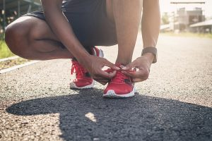 Man tying laces of new proper running shoes for post running injury